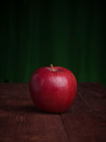 Juicy apple on a wood desk. And green background Royalty Free Stock Photos