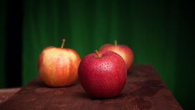 Juicy apples on a wood desk. And green background Royalty Free Stock Photos