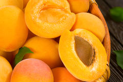 Juicy apricots in a basket. Fresh juicy apricots in a basket on a wooden background Royalty Free Stock Photography