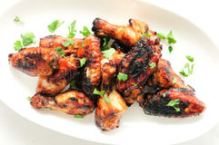 Juicy asian style chicken wings on a white plate with a white ba. Ckground Royalty Free Stock Image