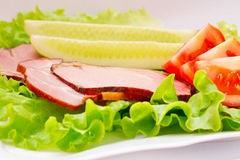 Juicy bacon on a plate with green salad, cucumbers and tomatoes. Bacon whith salad, cucumber and tomatoes on the plate Royalty Free Stock Image