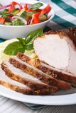 Juicy baked pork fillet and salad on the table. vertical Stock Photography