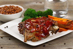 Juicy BBQ ribs and side dishes with water Royalty Free Stock Image