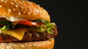 Juicy beef burger with cutlet, onion, vegetables, melted cheese, lettuce, sauce and topped sesame seeds. Isolated. Hamburger rotates on dark background, close stock footage