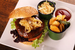 Juicy beef burger. Delicious juicy beef burger with caramelised onions and salad served with potato wedges on a white plate on a wooden table Stock Photos