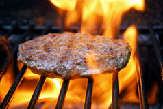 Juicy beef burger sizzling over hot flames on the barbecue Royalty Free Stock Photos