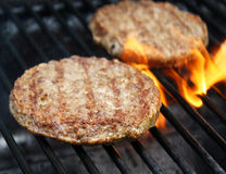 Juicy beef burgers sizzling over hot flames on the barbecue Stock Image