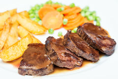 Juicy beef meat steaks with sauce, potatoes, carrots and peas on white plate, close-up. Selective focus.  Royalty Free Stock Images