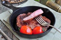 Juicy beef steak in a frying pan Royalty Free Stock Image