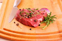 Juicy beef steak with spices and steel knife Royalty Free Stock Photo