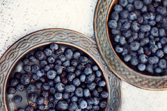 Juicy berries on a ceramic dish. The view from the top. Blueberries. The view from the top Stock Images