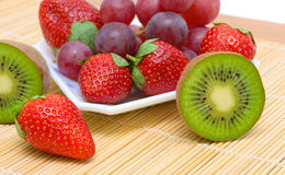 Juicy berries and fruit - kiwi, strawberries and grapes. Stock Image