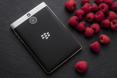 Juicy berries, high-contrast, BlackBerry smartphone. High quality close up photo of a BlackBerry smartphone lying on some shale surface. There is one of the most Stock Image