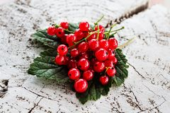 Juicy berries red currant on a green leaf on a white background of wood stock photo