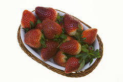 Juicy berries of ripe strawberries in a wicker basket on a white background. Juicy berries of ripe strawberries in a wicker basket on a white background Royalty Free Stock Photography