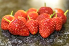 Juicy berries strawberry on delicate countertops in the kitchen in the luxurious interiors. Handful of fresh strawberries on the kitchen table Royalty Free Stock Image