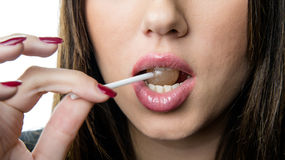 Juicy big lips of a woman bite a lollipop. Nice long thin finger with red nail polish,isolated white background royalty free stock photos