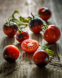 Juicy black tomatoes. And slices on wooden background Royalty Free Stock Photos