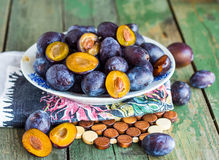 Juicy blue plum slices in a circular plate, horizontally Royalty Free Stock Image