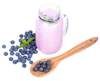 Juicy blueberries on a spoon isolated on a white background. Jar of blueberry milkshake. Preparation of summer dessert. Royalty Free Stock Images