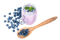 Juicy blueberries on a spoon isolated on a white background. Jar of blueberry milkshake. Preparation of summer dessert. Royalty Free Stock Photography