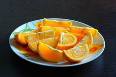 Juicy bright orange slices on a round plate royalty free stock photo