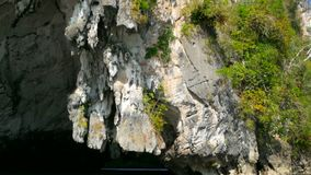 Boat slowly into the sea karst cave. Juicy bright tropical greens on the karst mountains under the blue sky of the southern province of thailand - phangnga stock video