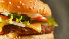 Juicy burger βόειου κρέατος με cutlet, κρεμμύδι, λαχανικά, λείωσε το τυρί, μαρούλι, σάλτσα και ολοκλήρωσε τους σπόρους σουσαμιού  απόθεμα βίντεο
