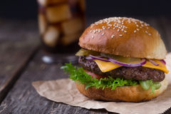 Juicy burger με την κρύα κόλα στο ξύλινο υπόβαθρο Στοκ φωτογραφία με δικαίωμα ελεύθερης χρήσης
