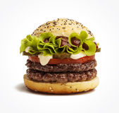 Juicy burger. Juicy double burger with pickles, tomatoes and lettuce on white background royalty free stock photo