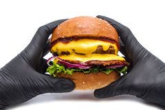 Juicy burger hamburger with cheese, onion, potatoes and salad on a white background in hands with gloves stock photography