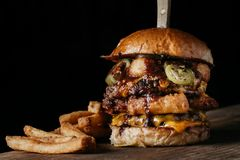Juicy Burger with onion rings and pickled jalapenos. Double Meat Burger with fried onion rings, cheese and pickled jalapenos Stock Photos