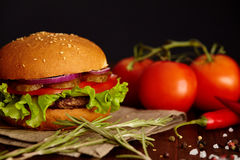 Juicy burger with tomatoes, spices and herbs on wooden table Stock Photo