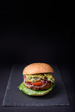 Juicy burger with turkey cutlet, sliced onion, tomato and avocado sauce served on black slate board, copy space. Juicy burger with turkey cutlet, sliced onion Royalty Free Stock Photos