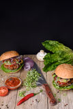 Juicy burgers with ingredients: salad, mushrooms, onion, beef, pepper and tomato sauce over wooden table. Black background and cop Royalty Free Stock Images