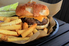 Juicy cheeseburger and crispy french fries Royalty Free Stock Image