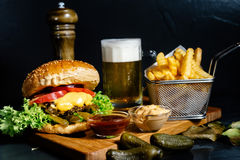 Juicy cheeseburger with fries, pickles, beer and coleslaw salad served by bistro. Mouth-watering juicy cheeseburger with fries, pickles, beer and coleslaw salad Royalty Free Stock Photos