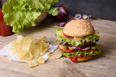 Juicy cheeseburger on wooden table with potato chips and ketchup. Royalty Free Stock Photography