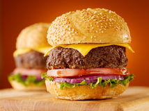Juicy cheeseburgers. Close up photo of two juicy cheeseburgers on wooden board, shot with selective focus Royalty Free Stock Photography