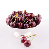 Juicy cherry fruit. Vase with cherry fruit on a white table Royalty Free Stock Photos