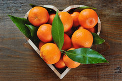 Juicy clementines in a heart shaped box on a wooden background Stock Photography