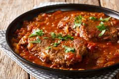 Juicy cube Swiss steak fried and slowly stewed in a spicy tomato. Sauce with vegetables close-up on the table. horizontal royalty free stock image