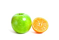 Juicy cut orange and green apple. Isolated on white background Stock Photo