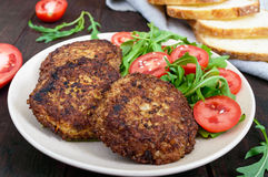 Juicy cutlets on a plate with a salad of tomatoes and arugula Stock Image
