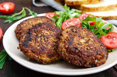 Juicy cutlets on a plate with a salad of tomatoes and arugula Royalty Free Stock Photography
