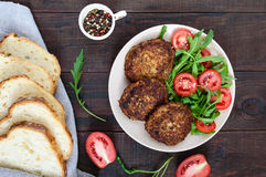 Juicy cutlets on a plate with a salad of tomatoes and arugula on a dark wooden background Royalty Free Stock Photo
