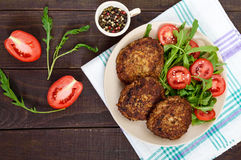 Juicy cutlets on a plate with a salad of tomatoes and arugula on a dark wooden background. Royalty Free Stock Photos