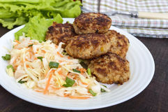 Juicy cutlets and salad with fresh vegetables: cabbage, carrots, greens Royalty Free Stock Photos