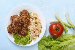 Juicy cutlets and salad with fresh vegetables: cabbage, carrots, greens on a white plate. Stock Photo