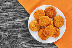 Juicy delicious breaded meat cutlets on white dish on old dark wooden boards, view from above Royalty Free Stock Images
